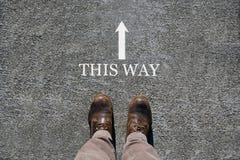 Mannens skor beskådar från över, ord hitåt och en pil som indikerar riktningarna med kopieringsutrymme för text arkivfoto