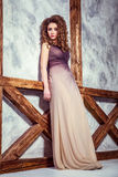 Mannequin avec la longue robe et la coiffure bouclée et maquillage posant près du mur avec le poteau en bois photos stock
