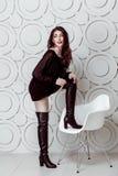 Mannequin avec le maquillage de coiffure et de smokey et lèvres rouges dans la robe noire et bottes posant sur la chaise blanche photos stock