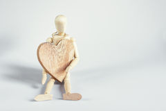 Mannequin with a big heart. The dummy sits on the board and holding a wooden heart Stock Photo