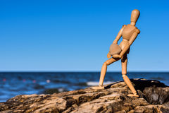 Mannequin carries a heavy stone. On the coast Stock Photo