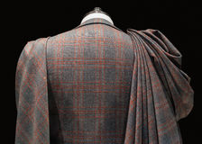 Mannequin in checkered suit with fabric folds. Rear close up view of a mannequin in checkered suit with fabric folds pinned to the shoulder Royalty Free Stock Photo