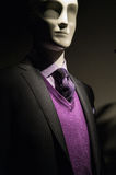 Mannequin in dark jacket with purple sweater. Dark picture of a mannequin in dark gray striped jacket with checkered shirt, purple V-neck sweater and purple tie Royalty Free Stock Images