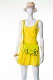 Mannequin in einem gelben Kleid, in einem Strohhut und in einer hellgrünen Handtasche Lizenzfreies Stockfoto