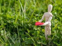 Mannequin en bois avec un coeur rouge sur ses mains dans l'herbe Concept de romantisme et d'amour Photographie stock