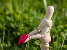 Mannequin en bois avec un coeur rouge sur ses mains dans l'herbe Concept de romantisme et d'amour Image libre de droits