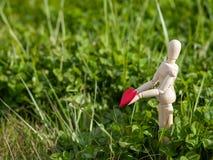 Mannequin en bois avec un coeur rouge sur ses mains dans l'herbe Concept de romantisme et d'amour Photos stock