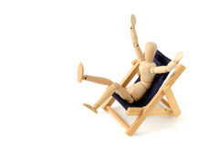 Mannequin en bois prenant le bain de soleil dans la chaise de plate-forme Image libre de droits