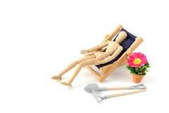 Mannequin en bois prenant le bain de soleil dans la chaise de plate-forme Photographie stock