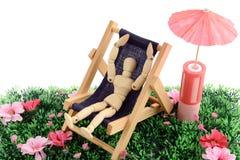Mannequin en bois prenant un bain de soleil dans une chaise Images stock