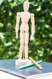 Mannequin en bois se tenant sur le paperbook de travail d'artiste Photos libres de droits