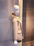 Mannequin en plastique d'enfant derrière une fenêtre de magasin de mode Images libres de droits