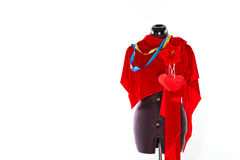 Mannequin with fabric and ribbon. Mannequin with a piece of red cloth and a measuring tape, a flower and a heart from a fabric. The concept of fashion and Royalty Free Stock Photos