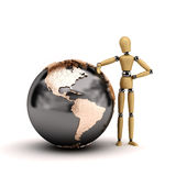 Mannequin with globe. Wooden mannequin leaning a big world globe showing North and South America Royalty Free Stock Photo