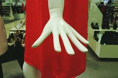 Mannequin hand. Close up of white mannequin hand and red outfit, in a retail fashion shop Stock Photos