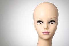 Mannequin head on grey background. Closeup of a female mannequin head Royalty Free Stock Images