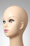 Mannequin head on grey background. Closeup of a female mannequin head Royalty Free Stock Image