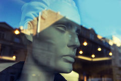 Mannequin head in a shop window with a reflection of the city Royalty Free Stock Image