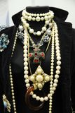 Mannequin with beautiful ornaments of gold with stones and pearl. Mannequin in a jacket with beautiful gold jewelry with colorful stones and pearls royalty free stock images