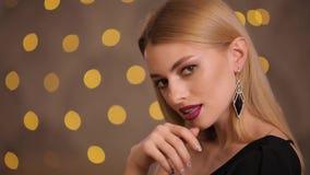 Mannequin met het mooie blondehaar stellen in gele lichten bokeh, langzame motie stock video