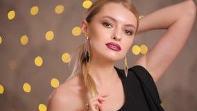 Mannequin met het mooie haar stellen in gele lichten bokeh, langzame motie stock videobeelden