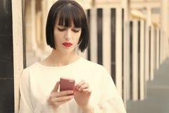 Mannequin met mobiel apparaat Vrouw met rood lippengebruik op smartphone in Parijs, Frankrijk Vrouw met donkerbruine haargreep royalty-vrije stock afbeeldingen