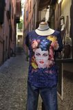 A mannequin outside a tourist`s hop in Varenna, Lake Como. A narrow street in Varenna,Lake Como with a mennequin  wearing a colourful t-shirt Stock Images