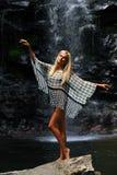 Mannequin posant devant la cascade Photos stock