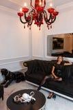Mannequin sexy dans la combinaison noire provocatrice de lingerie se reposant sur le divan en cuir dans l'intérieur moderne de lu Photos stock