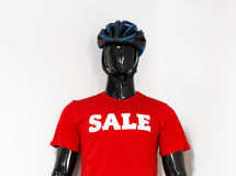 Mannequin in the showcase of sportswear. Male black mannequin figure of cyclist cloth in the showcase of sportswear in protective gear bicycle helmet and red t Royalty Free Stock Images