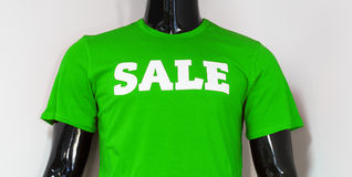Mannequin in the showcase of sportswear. Male black mannequin torso closeup in the showcase of sportswear in green t-shirt with sale text on it at the white Stock Photo