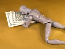 Mannequin Sleeping on Money. Mannequin using money for a pillow.  Metaphor for financial security.  Golden background Stock Image