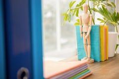 Mannequin und Stapel Bücher auf hölzernem Fensterbrett Lizenzfreie Stockfotos
