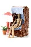 Mannequines en bois prenant un bain de soleil dans le jardin avec le cha de chaise et de plage Image libre de droits