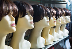 Mannequins with brown-haired and brunet style wigs on shelves. Of hair salon Royalty Free Stock Photography