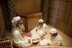 Mannequins dépeignant la scène du vieil homme musulman enseignant à Coran deux jeunes garçons Images stock