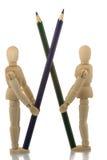 Mannequins die zich met twee gekruiste potloden bevinden Stock Foto's