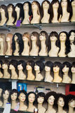 Mannequins with different style wigs on shelves Stock Photo