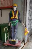 Mannequins einer Arbeitskraft draußen mit Schubkarre und Autobatterie in der Front, zeigen Attrappe an Stockfotografie