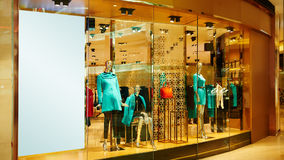 Mannequins in fashion shop window. With  blank advertising board in Hongkong center,go shopping in China,Asia Royalty Free Stock Images