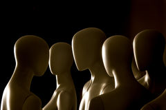 Mannequins. Group of mannequins male and female, different heights, black background, subtle natural light Stock Images