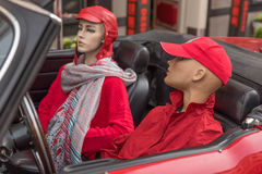 Mannequins in a red car. The upper torso female dummy in the passenger compartment of the car on the driver`s seat and the other in the passenger seat Stock Photos