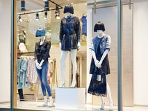 Mannequins standing in store window display. Of women s casual clothing shop in shopping mall Royalty Free Stock Photography