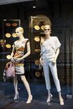 Mannequins standing in store window display of womens casual clothing shop. In shopping mall Stock Photos