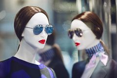 Mannequins standing in store window display. Of womens casual clothing shop in shopping mall Stock Images