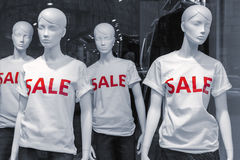Mannequins Wearing Sale T-Shirts. Shopping sale window display with four mannequins wearing t-shirts with text Sale Stock Photos
