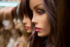 Mannequins in a wig shop Stock Images