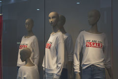 Mannequins. In the window of a youth clothing store in sweaters with the inscription `we are on sale Royalty Free Stock Photos