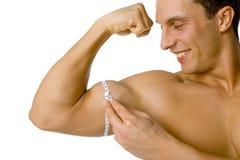 Mannes, der seinen zweiköpfigen Muskel mesuring ist Stockfoto