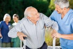 Mannes-und Frau-Krankenschwestern, die älteren Leuten helfen Lizenzfreie Stockfotos